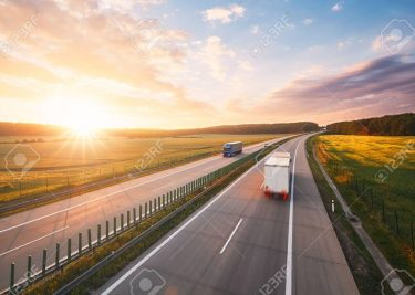 80120813-amazing-sunrise-on-the-highway-in-the-middle-of-the-countryside-transportation-and-cars-theme-